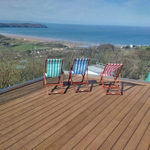 enhanced grain coppered oak millboard decking at the beach